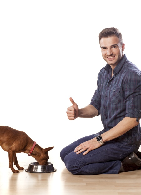 Young man feeding his dog and shows thumbs up